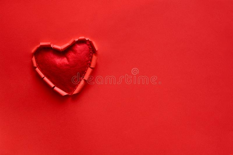 Ripped paper hole heart shaped with felt heart on red paper background. Valentine`s day celebration concept royalty free stock photo