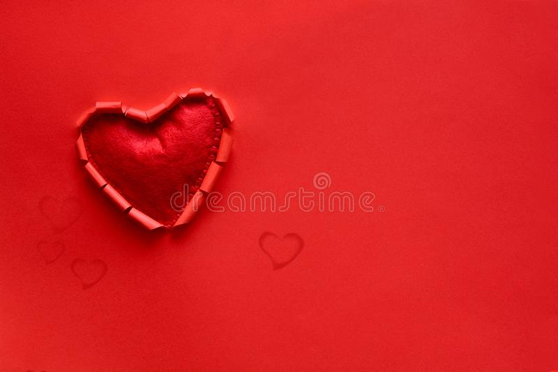Ripped paper hole heart shaped with felt heart on red paper background. Valentine`s day celebration concept royalty free stock photography