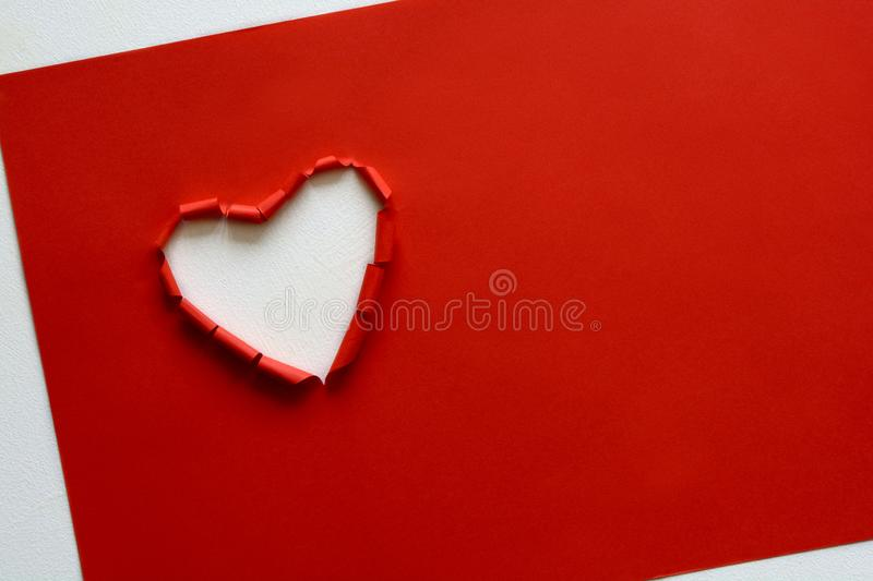 Ripped paper hole heart shaped on red paper background. Valentine`s day celebration concept royalty free stock photos