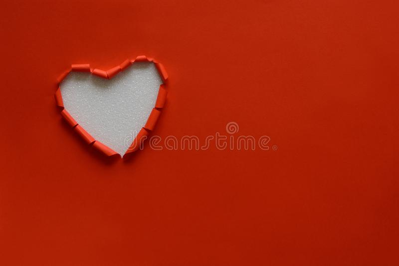Ripped paper hole heart shaped on red paper background. Valentine`s day celebration concept stock image