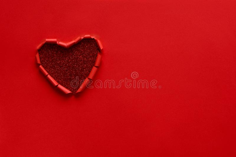Ripped paper hole heart shaped on red paper background. Valentine`s day celebration concept royalty free stock photo