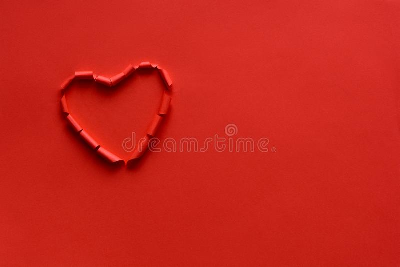 Ripped paper hole heart shaped on red paper background. Valentine`s day celebration concept stock photos