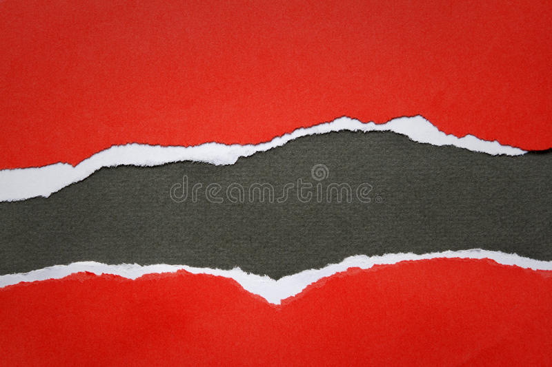 Ripped paper. Hole ripped in red paper on black background royalty free stock photos