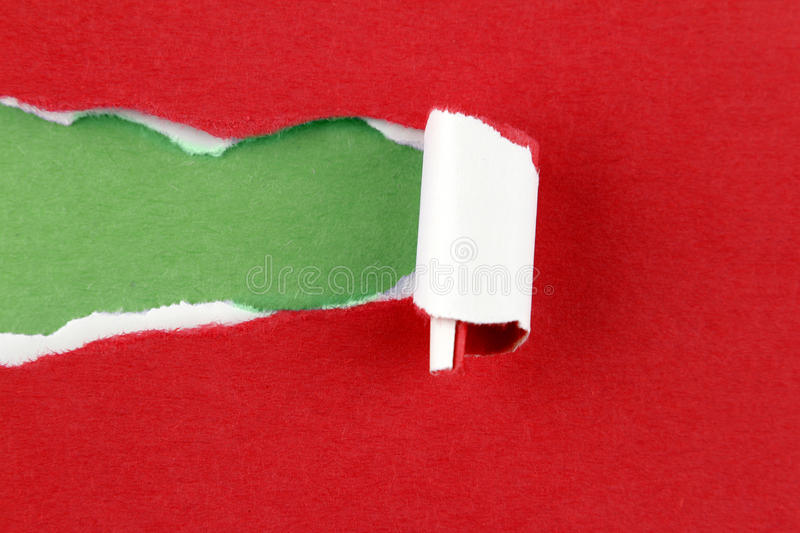 Ripped paper. Hole ripped in red paper on green background. Copy space royalty free stock images