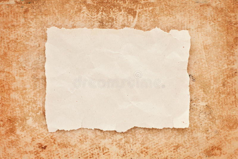 Ripped piece of old paper on grunge background stock photos