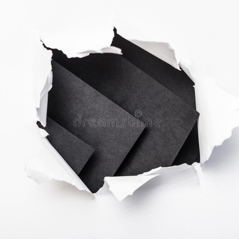 Ripped torn white paper abstract black background stock image