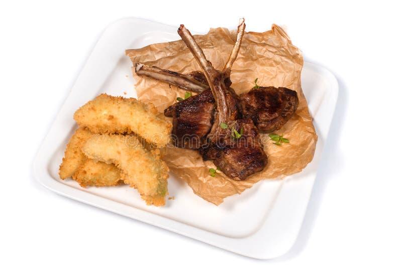 Rippen des gebratenen Lamms auf Papier und Gemüse im Teig in einer weißen Platte auf einem lokalisierten weißen Hintergrund stockbild