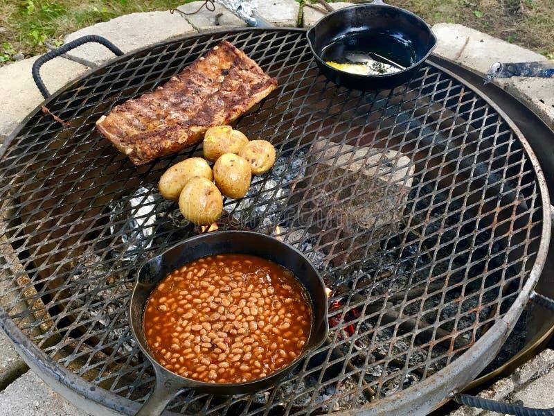 Rippen, gelbe Kartoffeln und gebackene Bohnen über einem Lagerfeuer stockfoto
