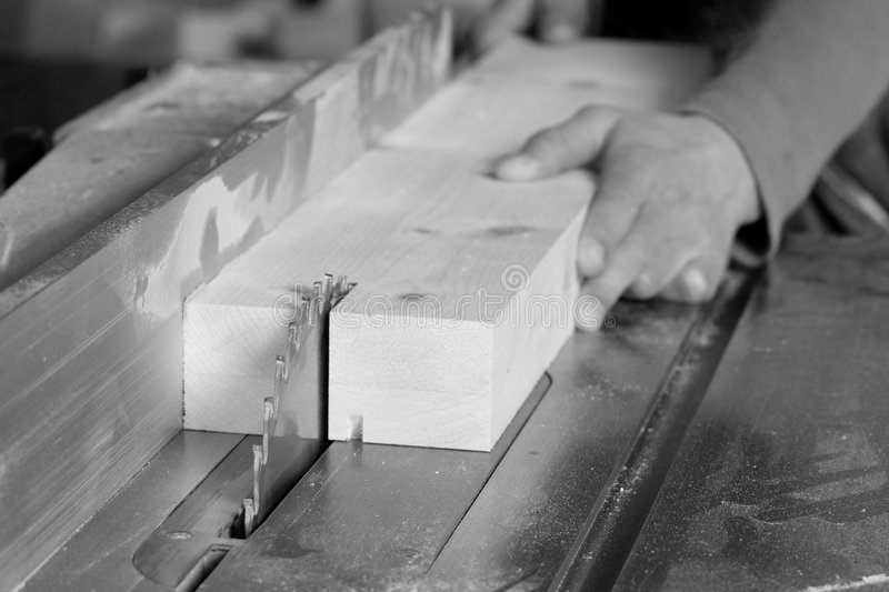 Ripping. A black and white photo of a board being ripped on a tablesaw stock photography