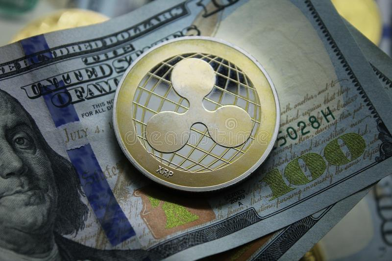 Ripple XRP Cryptocurrency. Ripple XRP golden cryptocurrency coin lying on a hundred dollars bills background.Electronic money exchange concept.Photo Illustration royalty free stock photos