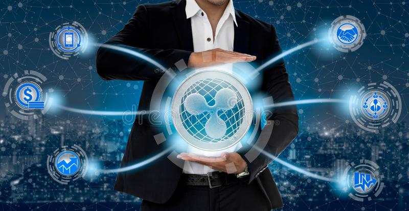 Ripple XRP and cryptocurrency investing concept. Ripple and cryptocurrency investing concept - Businessman holding Ripple (XRP) with mobile application business stock image