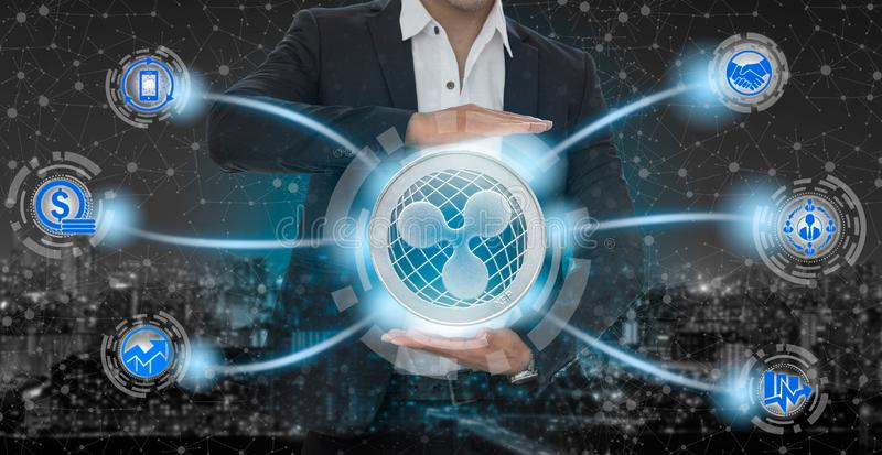 Ripple XRP and cryptocurrency investing concept. Ripple and cryptocurrency investing concept - Businessman holding Ripple (XRP) with mobile application business stock photography