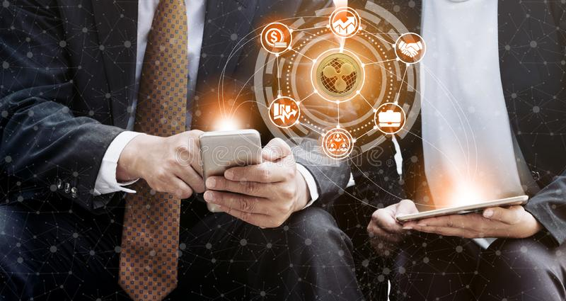 Ripple XRP and Cryptocurrency Trading Concept. Ripple and cryptocurrency investing concept - Businessman using mobile phone application to trade Ripple XRP with royalty free stock images