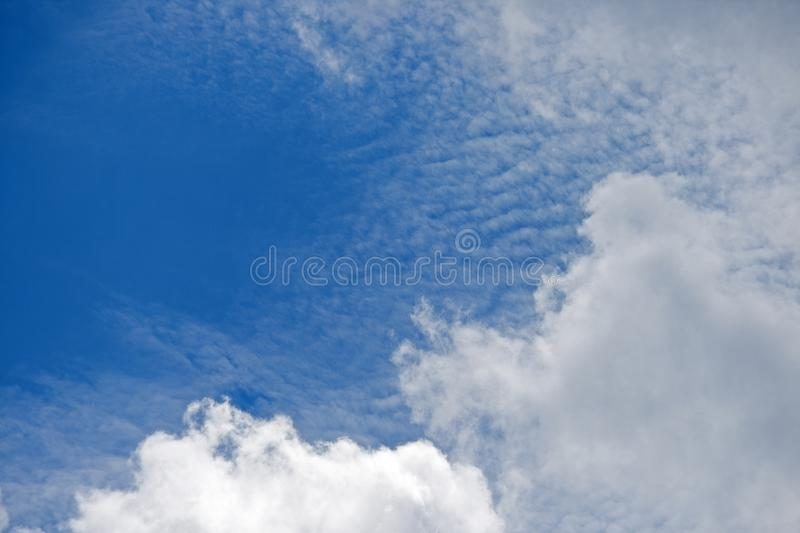 RIBBED CLOUD BEHIND LARGER WHITE CLOUDS. Rippled clouds against blue sky behind large clouds stock images