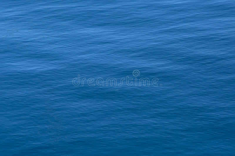 Rippling water texture. Deep blue calm rippling water background texture royalty free stock photography