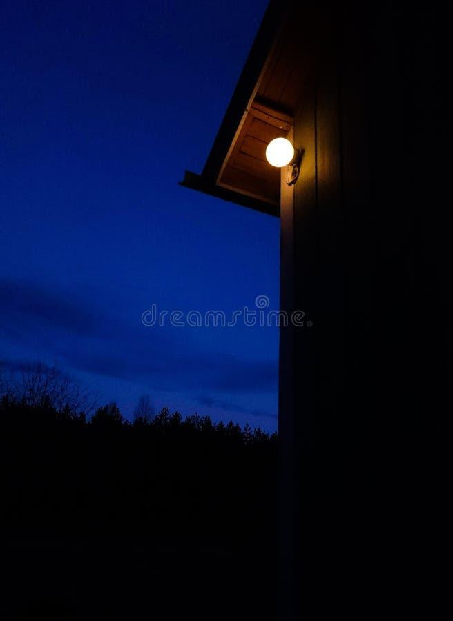 Ripresa di una lampadina accesa su una cabina di legno vicino agli alberi sotto un chiaro cielo azzurro durante la notte fotografia stock libera da diritti