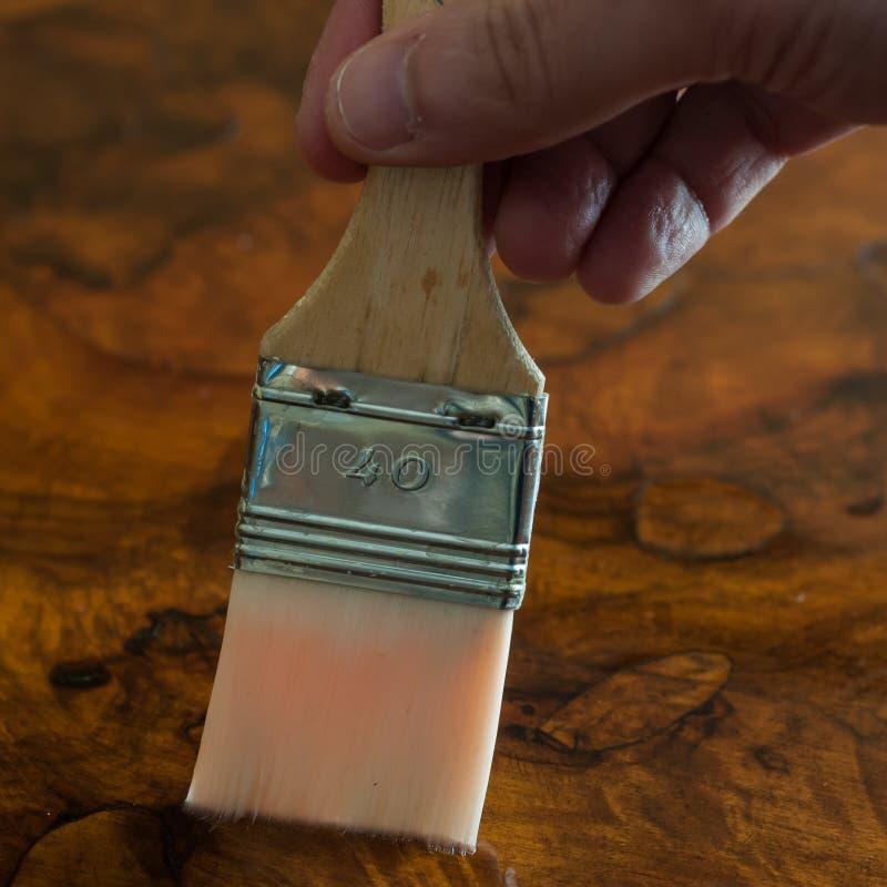 Ripristino della mobilia Passi la lubrificazione della tavola di legno con una spazzola fotografie stock