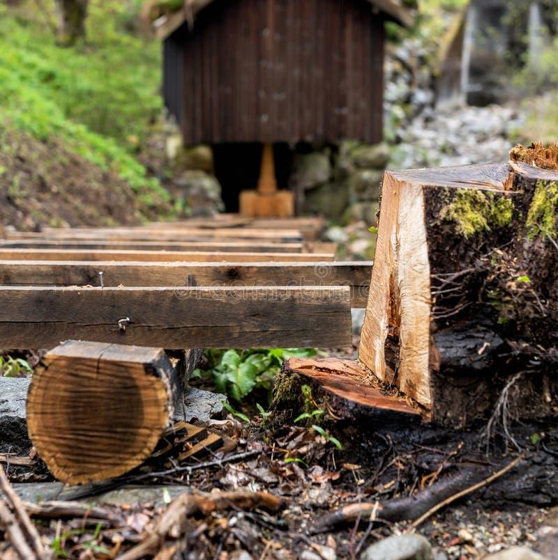 Ripristino di vecchio mulino a acqua di legno, lavoro in corso, fuoco sul taglio del ceppo di albero per fare stanza fotografia stock