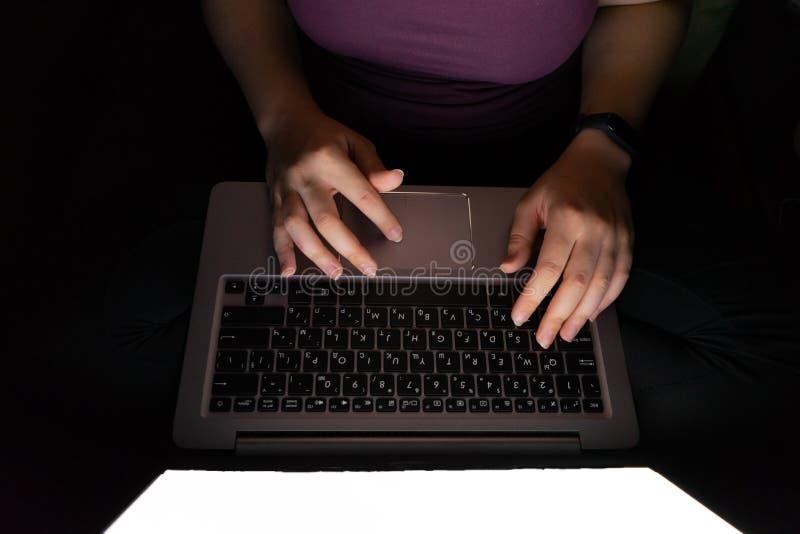 Riprogrammatore che per mezzo del computer portatile mani che scrivono tardi sul PC alla notte, vista da sopra Ragazza irriconosc fotografia stock libera da diritti