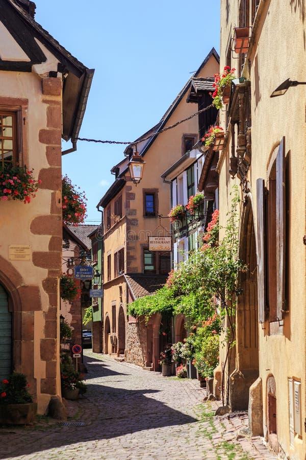 RIQUEWIHR, FRANCIA - 17 DE JULIO DE 2017: Calle pintoresca con las casas coloridas tradicionales en el pueblo de Riquewihr en la  fotos de archivo