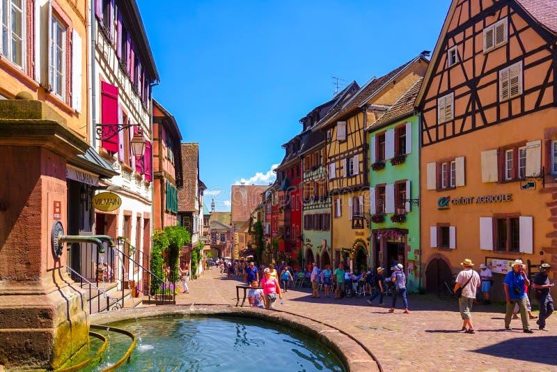 Riquewihr, Francia 23 de junio de 2016: Los turistas están caminando en la calle principal de las compras en Riquewihr imagen de archivo