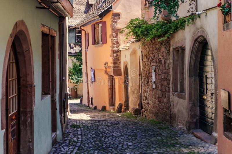RIQUEWIHR, FRANCIA - 17 LUGLIO 2017: Via pittoresca con le case variopinte tradizionali nel villaggio di Riquewihr sull'itinerari fotografie stock