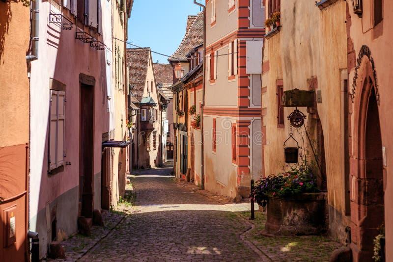 RIQUEWIHR, FRANCIA - 17 LUGLIO 2017: Via pittoresca con le case variopinte tradizionali nel villaggio di Riquewihr sull'itinerari fotografia stock libera da diritti