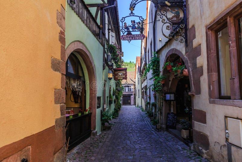 RIQUEWIHR FRANCJA, LIPIEC, - 17, 2017: Malownicza ulica z tradycyjnymi kolorowymi domami w Riquewihr wiosce na alsatian wino tras zdjęcia stock
