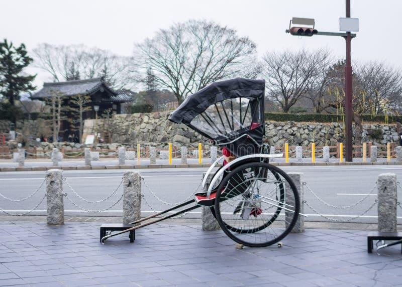 Riquexó japonês tradicional antigo estacionado no passeio fotos de stock royalty free