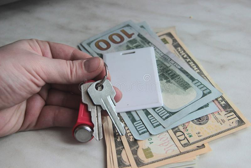 Riqueza y riquezas representadas por el dinero y las llaves del efectivo llaves del apartamento de los dólares, falta de definici imagenes de archivo