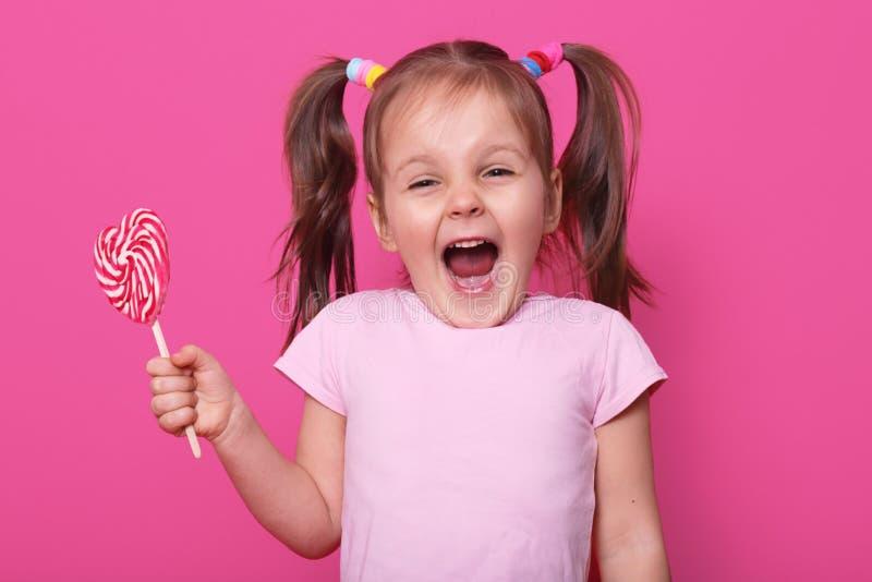 Rir gritando a menina bonito abre sua boca extensamente, mostrando os dentes, realiza em um pirulito saboroso brilhante do cora?? foto de stock royalty free