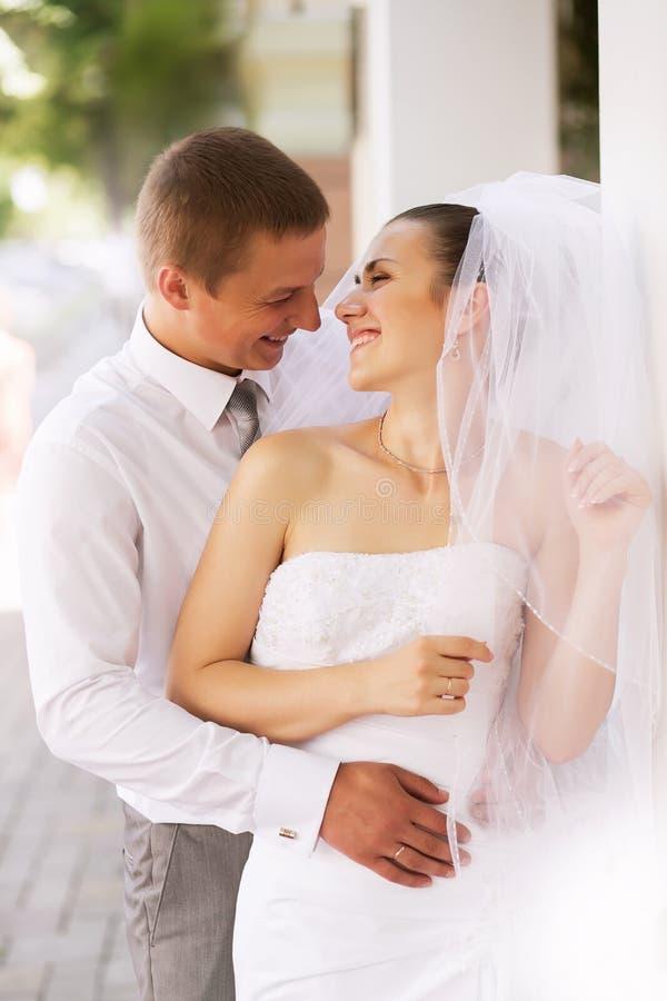 Rire heureux de jeunes mariés image stock