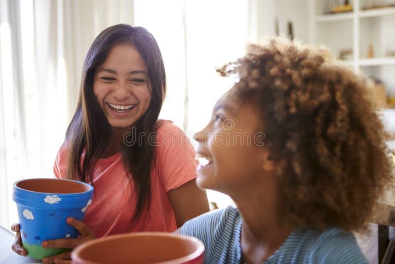 Rire la pré-adolescente et sa copine aînée tenant des pots de plantes qu'ils ? décorés de peintures à la maison, accent sélectif, photographie stock