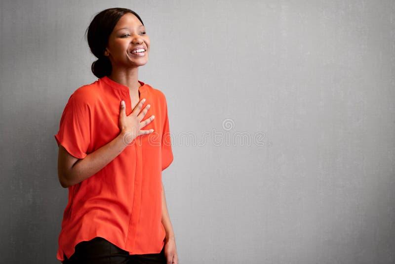 Rire occupé d'entrepreneur africain heureux avec une main sur le coffre photo libre de droits