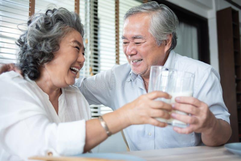 Rire supérieur asiatique heureux et lait boisson de couples des verres images stock