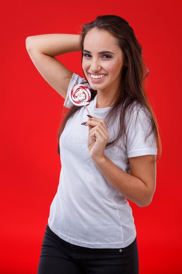 Rires de jeune fille heureusement et prise dans des mains une lucette douce ronde Sur un fond rouge photos libres de droits