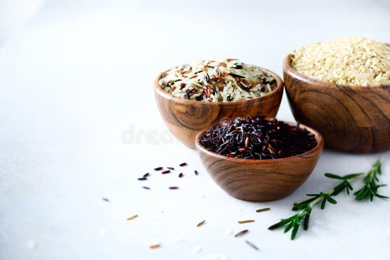 Ris för vita ris för jasmin för brunt, svart och röd, Det blandade sortimentet av korn i träbunkar på grå färger hårdnar bakgrund royaltyfri fotografi