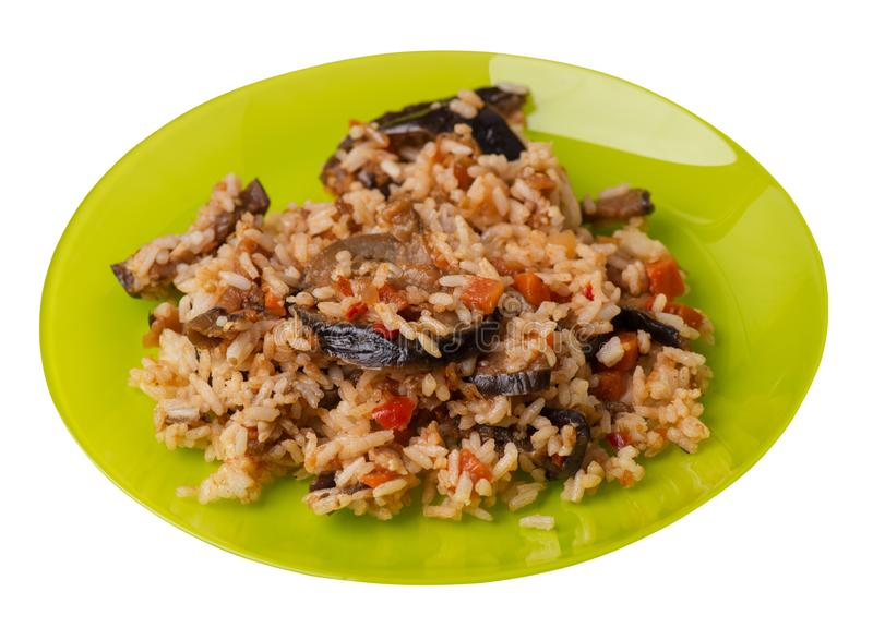 Ris med den bräserade zucchinin med tomater och peppar på en platta Ris med gr?nsaker som isoleras p? vit bakgrund vegetarian arkivbild