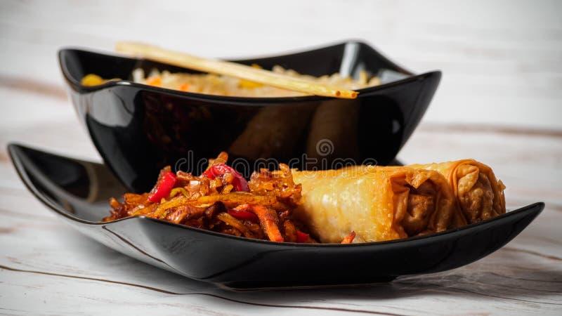Ris med grönsaker, Vår-rullar och kött arkivfoto