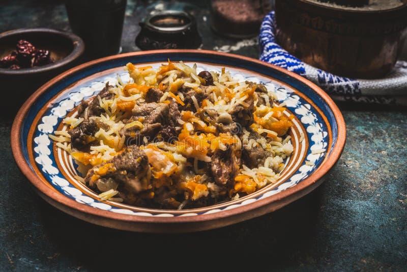 Ris med kött och grönsaker i lantlig platta på den mörka trätabellen Pilaff nationell maträtt royaltyfri fotografi
