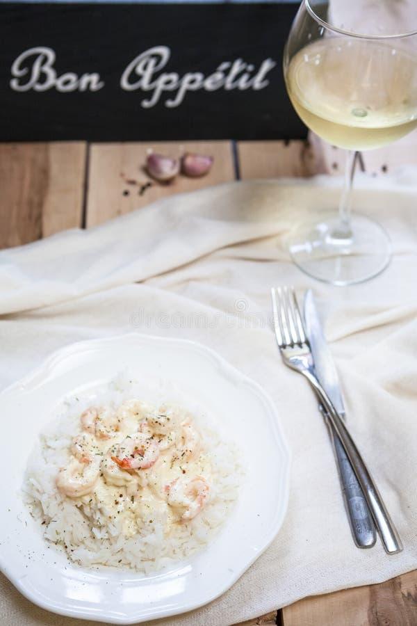 Ris med räkor och vitt vin på tabellen royaltyfria foton
