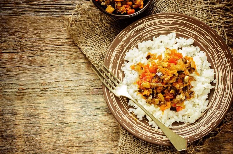 Ris med sås av aubergine, peppar och tomater arkivfoto