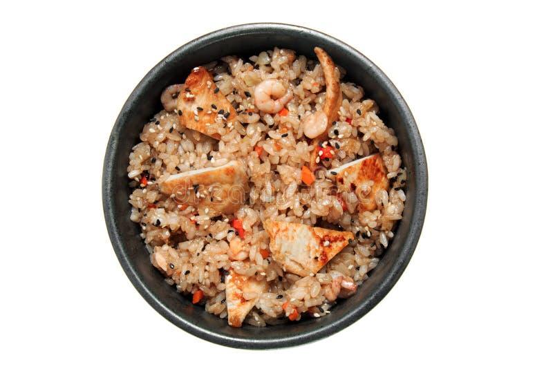 Ris med stekt kyckling, räkor, grönsaker och sesam i den svarta bunken bakgrund isolerad white royaltyfri fotografi