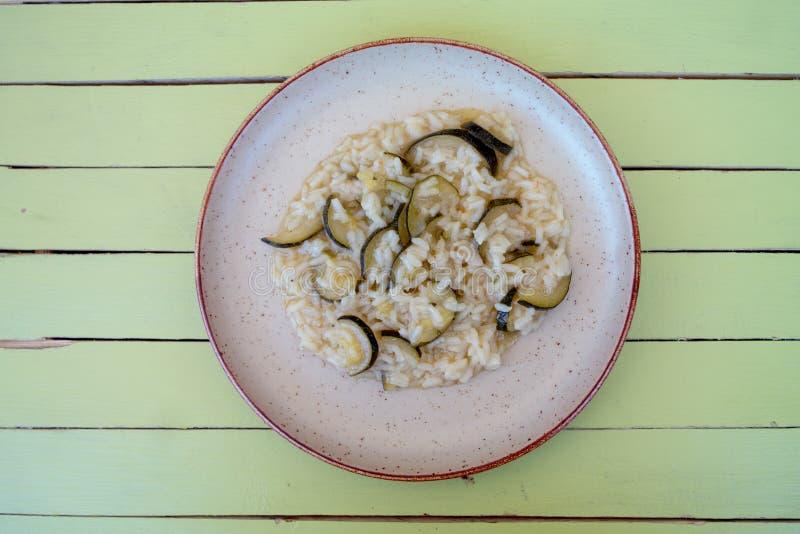 Ris med zucchinin i en lantlig maträtt på grönt trä från över arkivfoto