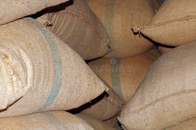 Ris plundrar, rissäckar i lagret, hög av rissäckar i lager, rissäckar för bakgrund arkivfoton