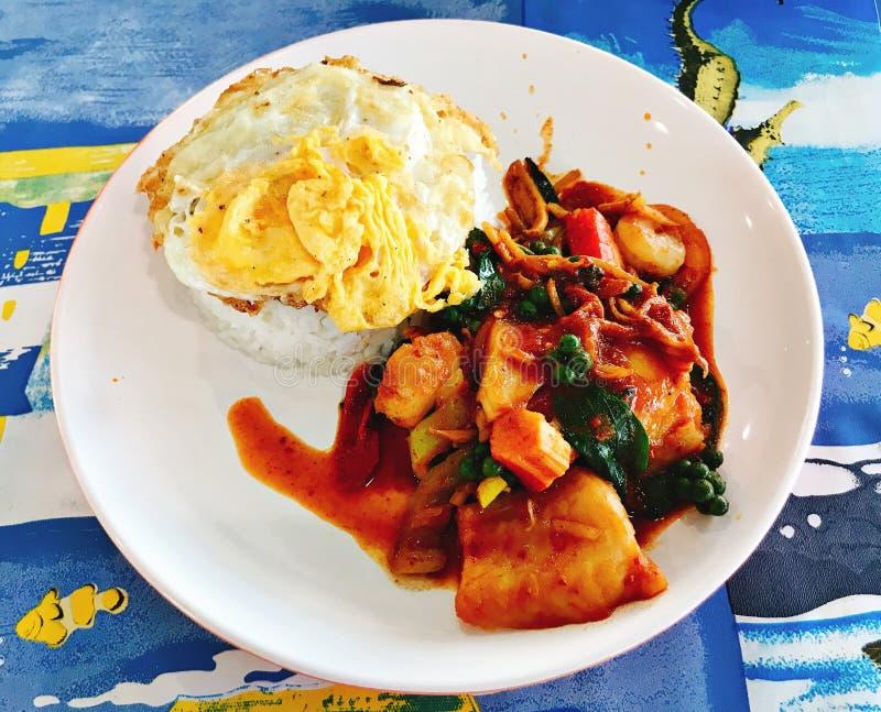 Ris som överträffas med det stekte ägget, kryddig uppståndelse stekt skaldjur med röd currydeg royaltyfri fotografi
