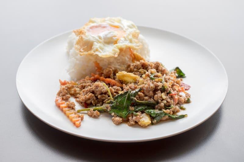 Ris som överträffas med stekt under omrörning griskött och basilika royaltyfri fotografi