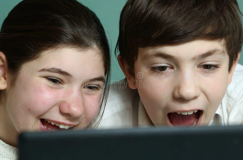 Risa adolescente de la comedia del reloj de la hermana y del hermano imagen de archivo