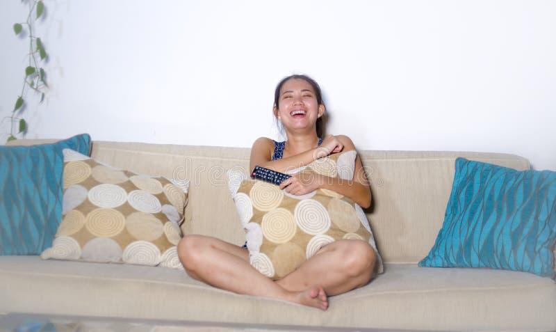 Risa china asiática linda joven de la mujer feliz sentando en casa la show televisivo del sofá del sofá o la película de observac imagenes de archivo