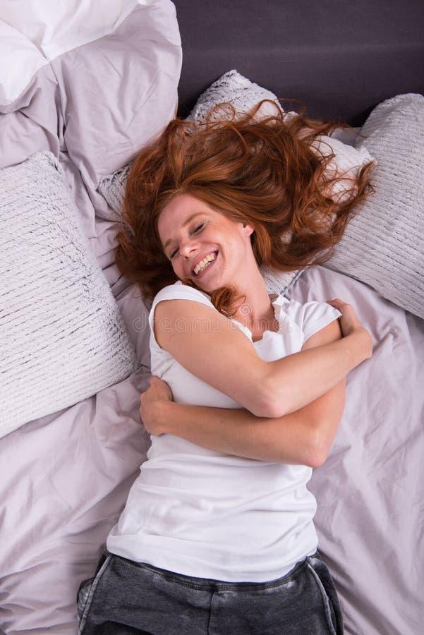 Risa de mentira de la mujer pelirroja joven en su cama fotos de archivo